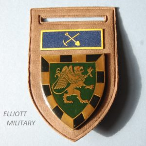 badge with griffon on a shield and crossed pick and shovel above