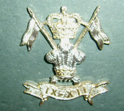 badge with crossed lances and crown above the Prince of Wales feathers on top of scroll with Roman numerals