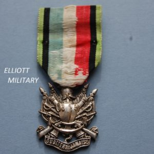 medal with coat of armour on crossed rifles and swords above an anchor and scroll