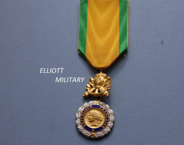 medal with head within a circle and wreath below a coat of armour