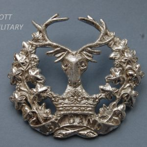 badge with stags head above a crown and scroll within a wreath
