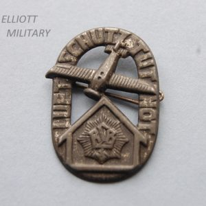 badge with aeroplane above a house within an oval band reading luftschuts tut not