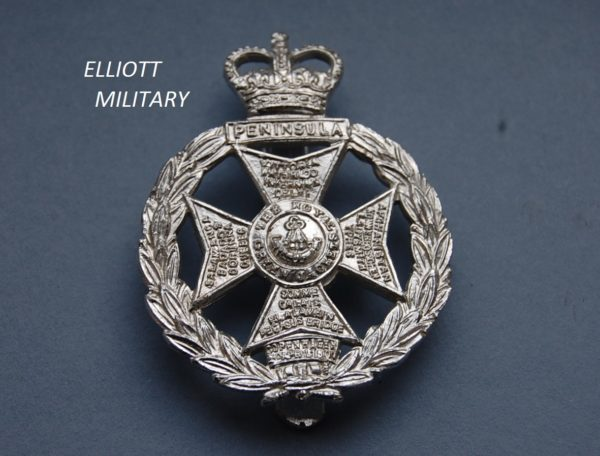 Badge with a Maltese cross with battle honours within a wreath below a crown