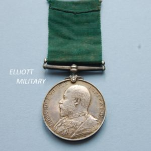 medal showing the side profile of King Edward the seventh with green ribbon