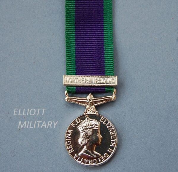 Miniature medal with queens head with purple ribbon with green edges