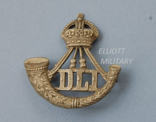 badge with a crown above a strung bugle and letters DLI