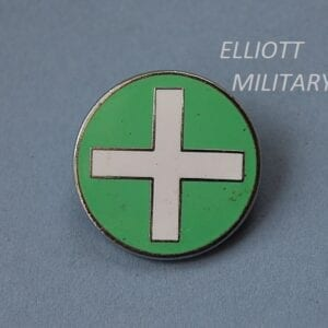 circular badge in green with white cross in centre
