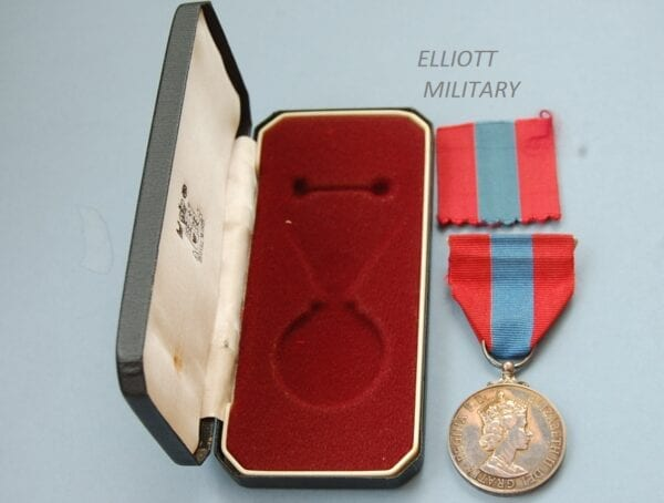 medal with Queen Elizabeth 11 side profile on red ribbon with central blue stripe