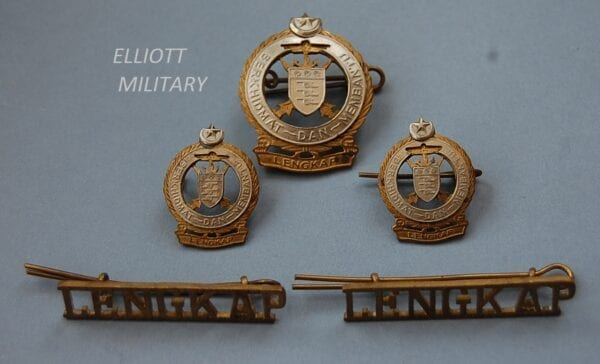 5 badges, three with shield depicting 3 cannons with crossed kris knives and anchor within a titled scroll below a crescent moon and star. The other 2 badges reading LENGKAP