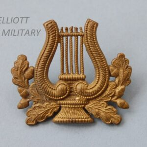 brass badge with oak leaves around a lyre