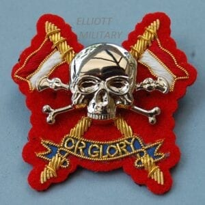 badge with metal scull and crossed bones mounted on cloth backing badge with crossed lances and scroll reading Or Glory