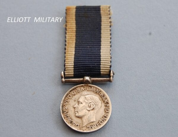 miniature medal with the head of King George the sixth on a blue ribbon with white edges