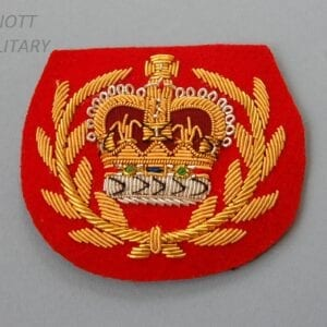 red backed cloth badge with wire embroidery crowm within wreath