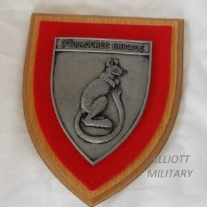 red felt backed shield with standing desert rat and text reading 7th. Armoured Brigade