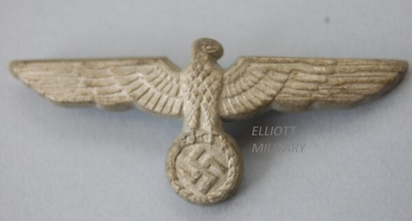 badge with eagle clutching a swastika within a wreath.