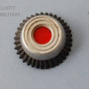 small circular cap badge with red centre surrounded by silver and black