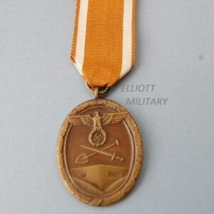 bronzed oval medal with eagle and swastika above a crossed shovel and sword above defensive fortifications all within a wreath