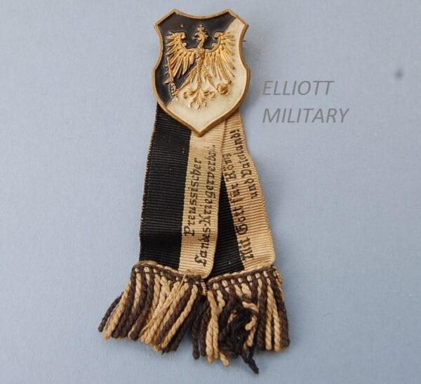 Pin badge with eagle on a black and white shield with ribbons attached