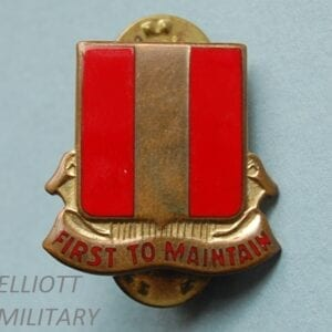 badge with red and gold striped shield and scroll underneath reading First to maintain
