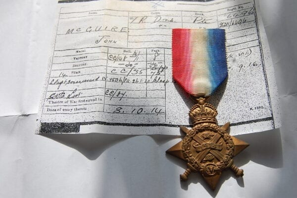 Bronze star shaped medal with crossed swords and wreath below a crown with central scroll reading 1914