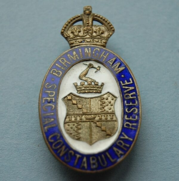 Oval badge with Birmingham City crest below a crown