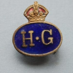 oval badge with crown above the letters H.G on a blue enamel field