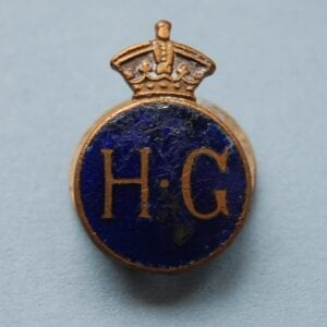 badge with crown above the letters H.G on a blue enamel field
