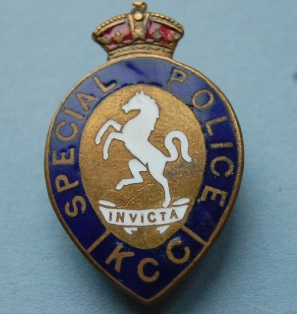 tear shaped badge with crown above a horse on hind legs with a scroll reading INVICTA below and the words SPECIAL POLICE KCC around the outside