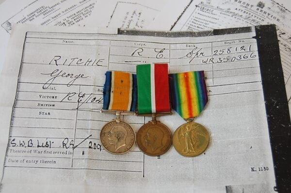 A trio of medals, one silver with King George the 5th then one bronze the same and a yellow bronze one with winged angel