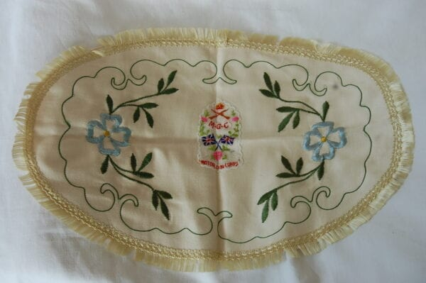 tablecloth with the embroidery reads - Motor Gun Corps with crown above crossed rifles and scroll below with M.G.C. and crossed union flags below.