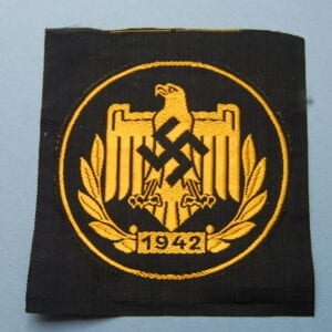 CLOTH BADGE with eagle and swastika above a 1942 dated wreath