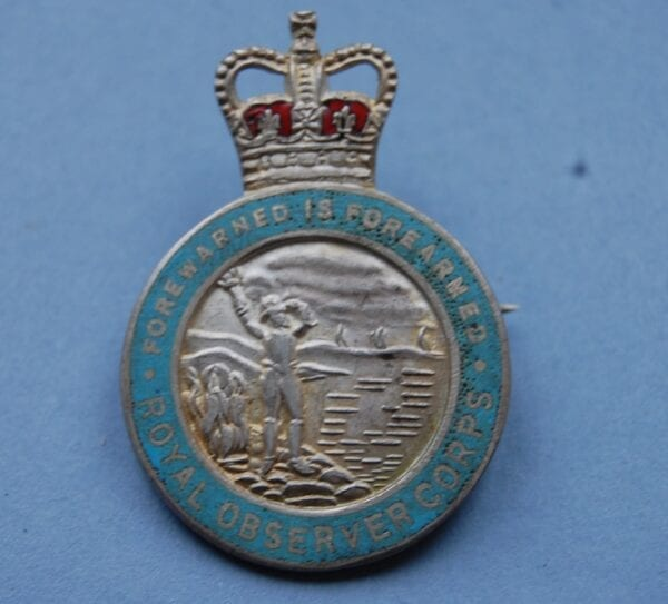 circular badge with an Elizabethan lookout holding a flaming torch below a crown and wording around the edge reading FOREWARNED IS FOREARMED ROYAL OBSERVER CORPS