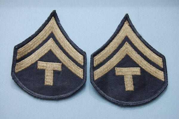 pair of cloth badges with two inverted chevrons above a capital letter T