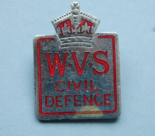 small pin badge with crown above the letters WVA CIVIL DEFENCE in red ename