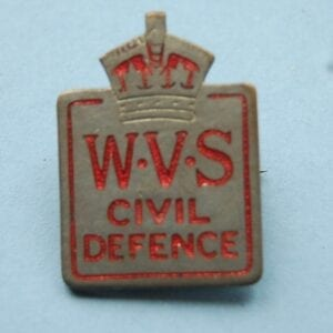 small pin badge with crown above the letters WVA CIVIL DEFENCE in red enamel