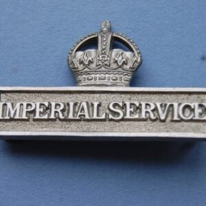 badge with the words IMPERIAL SERVICE within a rectangular block below a crown