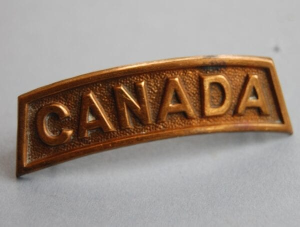 solid brass curved shoulder title reading CANADA