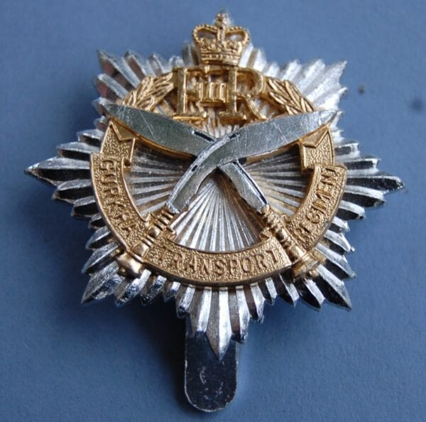 badge with crossed kukri knives on top of a star within a wreath with E11R royal cypher and crown above