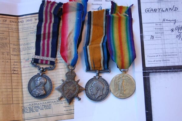 row of 4 medals with papers